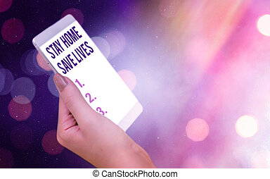 Conceptual hand writing showing Stay Home Save Lives. Business photo showcasing lessen the number of infected patients by not leaving the house Modern gadgets white screen under colorful bokeh background.