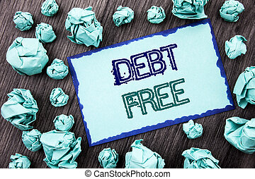 Conceptual hand writing text showing Debt Free. Concept meaning Credit Money Financial Sign Freedom From Loan Mortage written on Sticky note paper folded paper on the wooden background.
