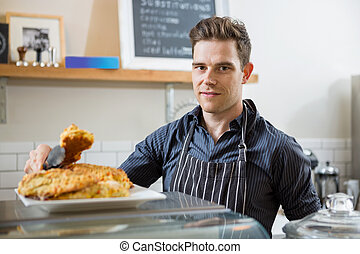 Confident Cafe Owner Holding Sweet Food In Tongs