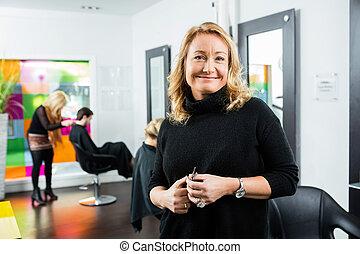 Confident Female Hairdresser Holding Scissor