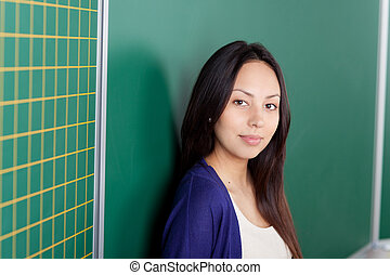 confident female student leaning against board