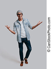 Confident in his style. Full length of handsome young man in jeans shirt gesturing and looking at camera while standing against grey background