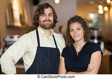 Confident Owners Standing Together In Cafe