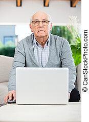 Confident Senior Man Using Laptop At Nursing Home Porch