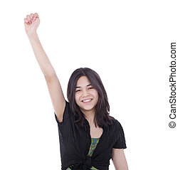 Confident, young biracial teen girl, raising one arm in air with expression of success.