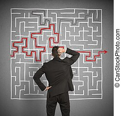 Confused business man seeks a solution to the labyrinth