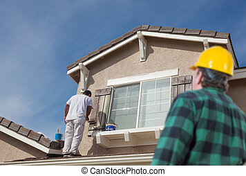 Contractor Overlooking Painter Paitning House