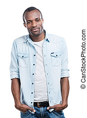 Cool and carefree. Handsome young black man holding hands in pockets and smiling at camera while standing against white background