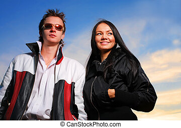 Cool looking young couple over dramatic sunset sky