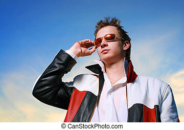 Cool young man in sunglasses over sunset sky