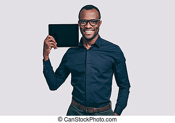 Copy space on his tablet. Handsome young African man carrying digital tablet on his shoulder and smiling while standing against grey background