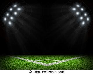 Corner of empty green field with bright spotlights