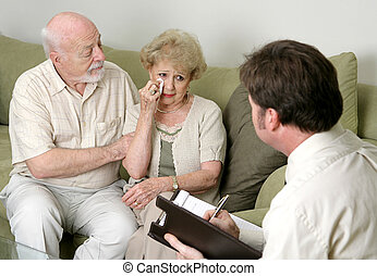 A senior couple in counseling - either grief counseling or marriage counseling. The wife is crying and the husband is wiping her tears and trying to console her.