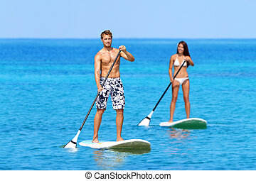 Couple Doing Stand Up Paddleboarding On Ocean