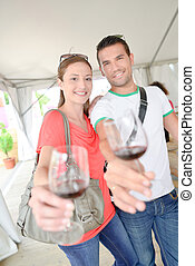 Couple holding glass of wine each in outstretched arm