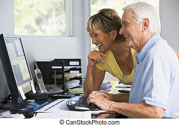 Couple in home office with computer and paperwork smiling