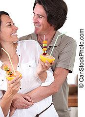 Couple in kitchen holding dessert