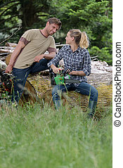 couple in the woods with chainsaws