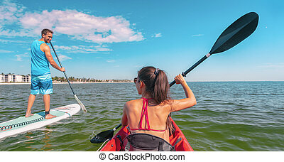 Couple kayaking and paddle boarding fitness man in ocean Paddleboard beach people on stand-up paddle boards surfing in Tourists kayakers woman and man enjoying SUP kayak watersport Keys, Florida, USA