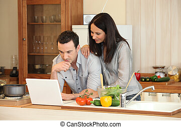 Couple looking at a laptop in their kitchen