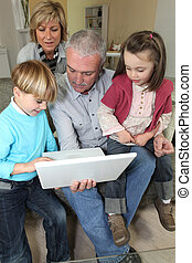 Couple looking at a laptop with their grandchildren