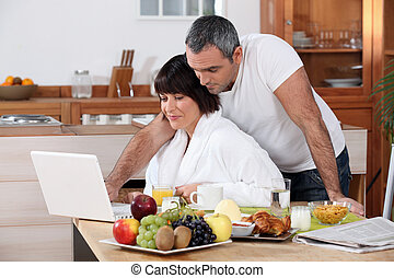 Couple looking at their laptop during breakfast
