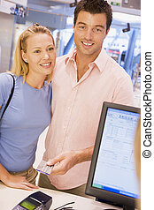 Couple making purchase with credit card