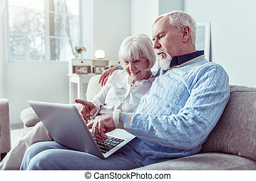 Couple of modern grandparents looking at laptop while having video chat