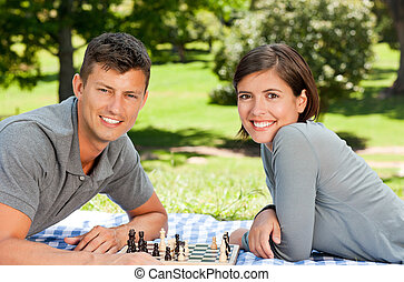 Couple playing chess in the park