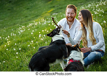 Couple playing with their dogs in the park