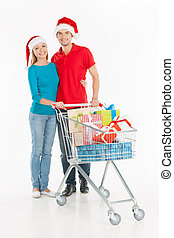 Couple shopping. Cheerful young couple standing near shopping cart and smiling while isolated on white