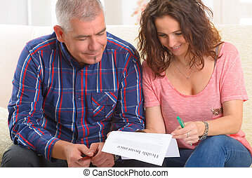 Couple signing health insurance contract
