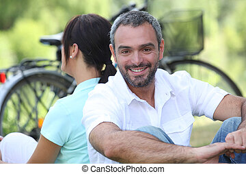 Couple sitting by their bikes in the countryside