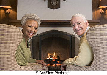 Couple sitting in living room by fireplace smiling