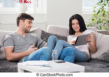 couple sitting on a couch with tablet computers