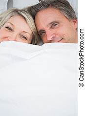 Couple smiling at camera from under the covers