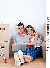 Couple using a laptop amongst cartons