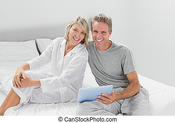 Couple using their digital tablet smiling at camera