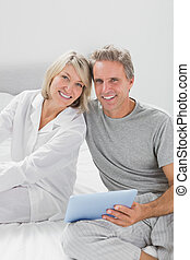 Couple using their tablet pc smiling at camera