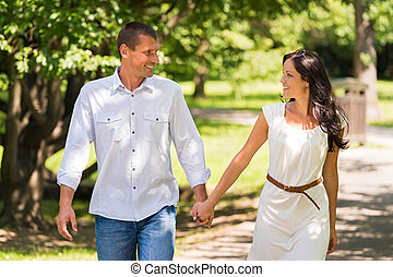 Couple walking and laughing in a park