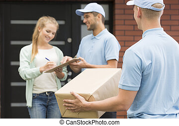 Courier with package and woman signing a form