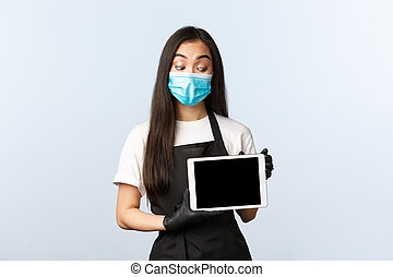 Covid-19 pandemic, social distancing, small business and preventing virus concept. Coffee shop owner or barista in medical mask and gloves showing clients easy way order coffee home, digital tablet