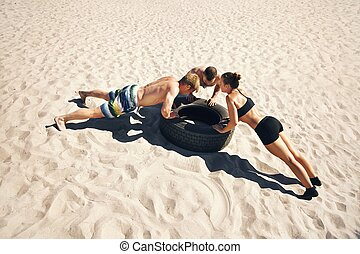 A group of crossfitters doing push-ups on tire