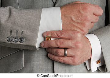 Close up of man in business suit adjusting cuff links