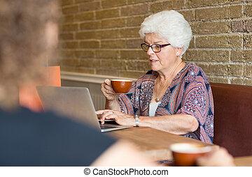 Senior female customer using laptop while having coffee in cafe
