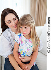 Cute blond girl sitting on her mother's lap