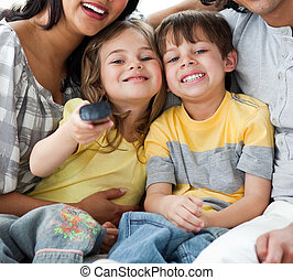 Cute children watching TV with their parents