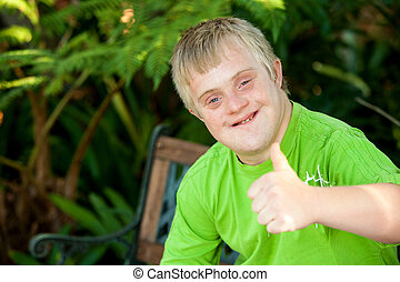Close up portrait of cute handicapped boy showing thumbs up outside.