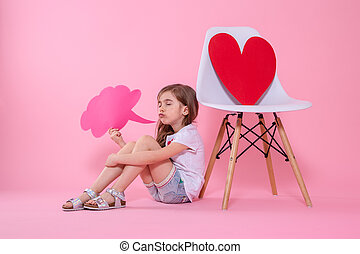 Cute little girl with speech icon on colored background