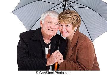 senior husband and wife under an umbrella